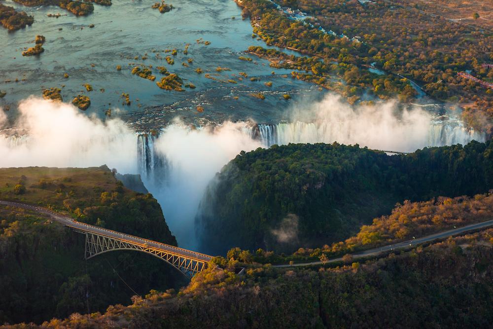 Reise in Sambia in Afrika. Aus der Luft sind die Viktoriafälle in der Nachmittagssonne zu sehen. Man erkennt von oben eine Brücke und eine Strasse.