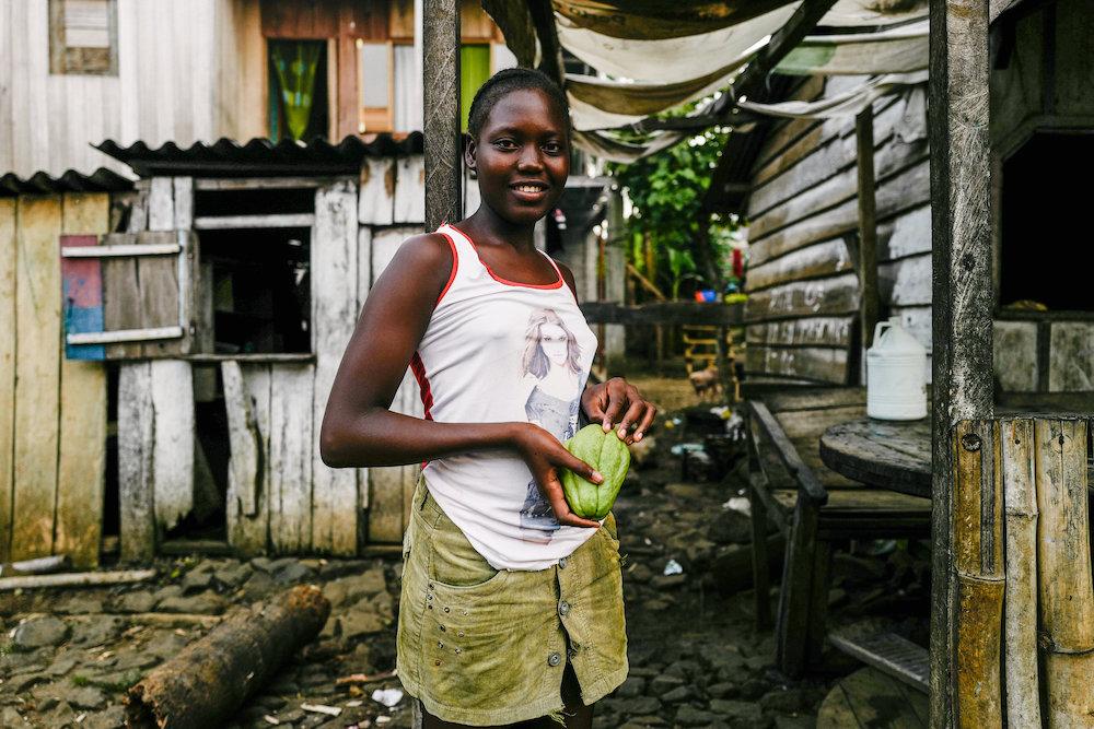 Reise in Sao Tome und Principe in Afrika. Eine einheimische Frau steht vor ihrem Haus und hält eine Kakaofrucht in der Hand.