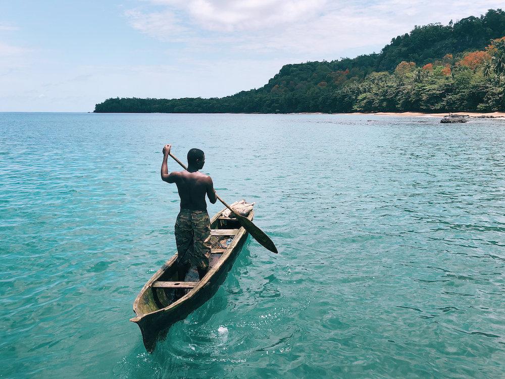 Reise in Sao Tome und Principe in Afrika. Ein einheimischer Fischer rudert mit seinem Boot der dicht bewaldeten Insel Küste entlang.
