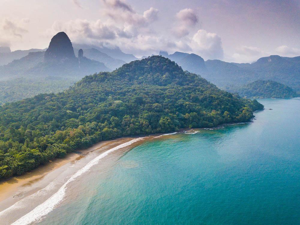 Reise in Sao Tome und Principe in Afrika. Ansicht auf die Insel aus der Luft, die Hügel sind von Regenwald bedeckt, markante Basaltnadeln ragen vereinzelt empor, Sandstrand umgibt die Küste der Insel, türkise Wellen brechen sich.