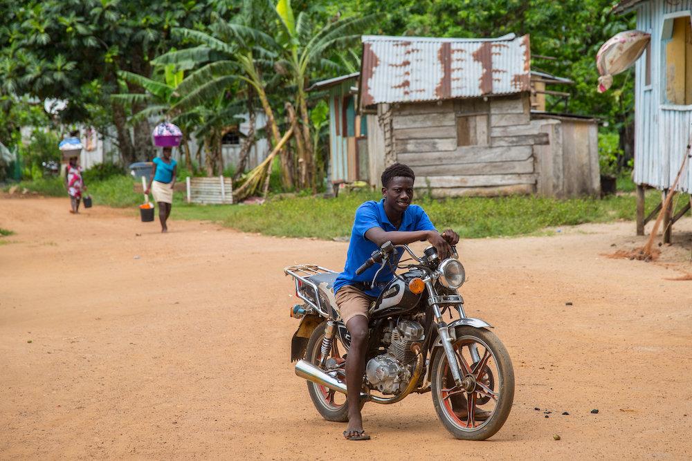 Reise in Sao Tome und Principe in Afrika. Ein einheimischer Mann posiert auf einem Motorrad auf der Strasse. Im Hintergrund sind weitere Dorfbewohner und Hütten zu erkennen.