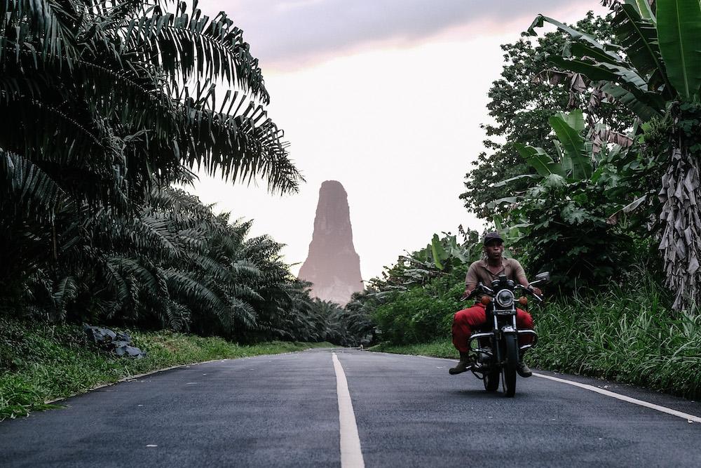 Reise in Sao Tome und Principe in Afrika. Ein einheimischer Mann fährt auf seinem Motorrad die Strasse, die von Dschungel umgeben ist, entlang. Im Hintergrund erhebt sich der Pico de Principe.