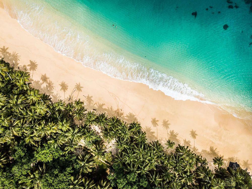 Reise in Sao Tome und Principe. Blick aus der Vogelperspektive auf die Küste der Insel, zu sehen ist der Dschungel mit Palmen, Sandstrand und Meer.