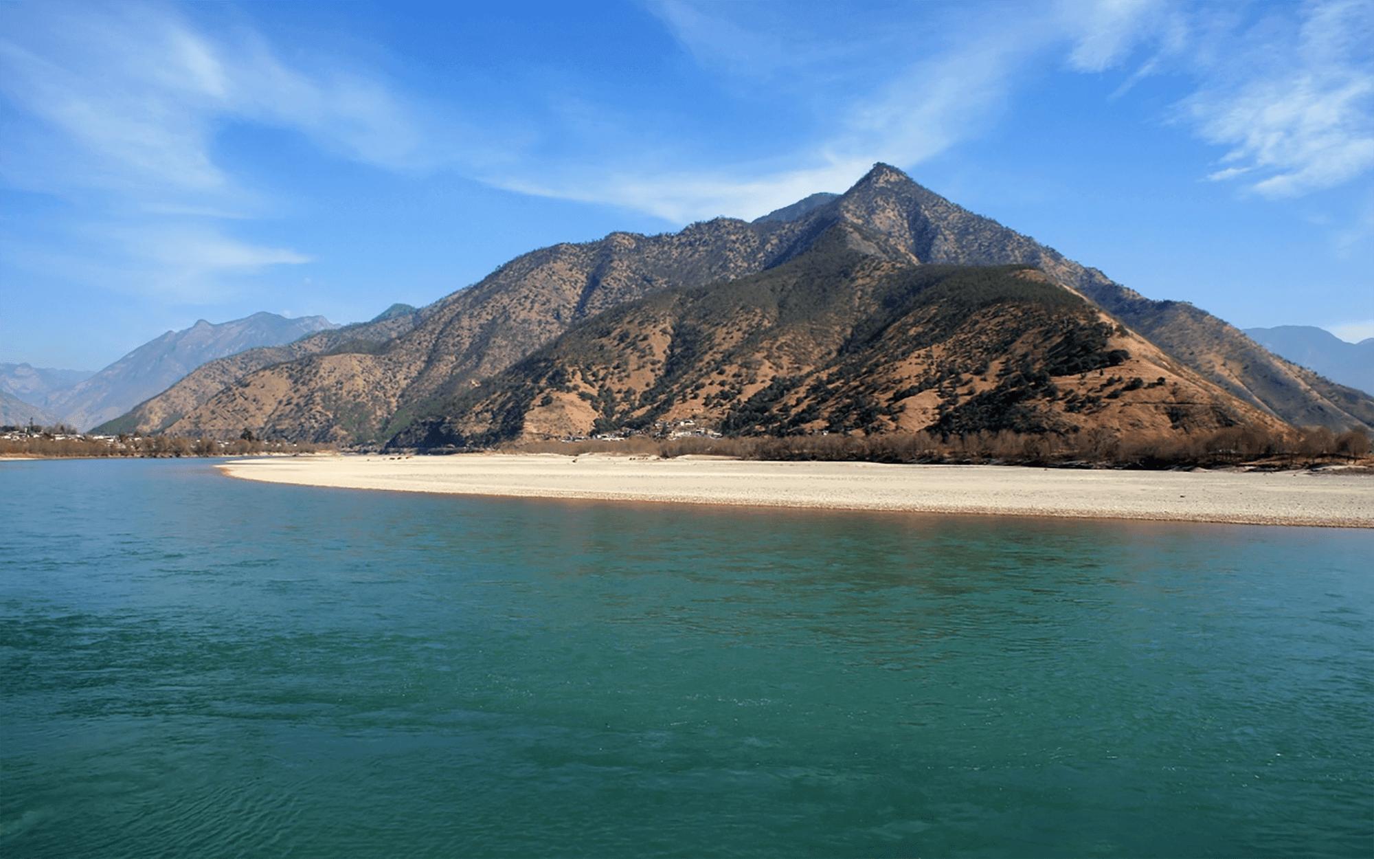 Reise in Yunnan in China. An der Küste zum Meer erhebt sich ein hoher, karger Berg, davor liegt ein kurzer Streifen Sandstrand.