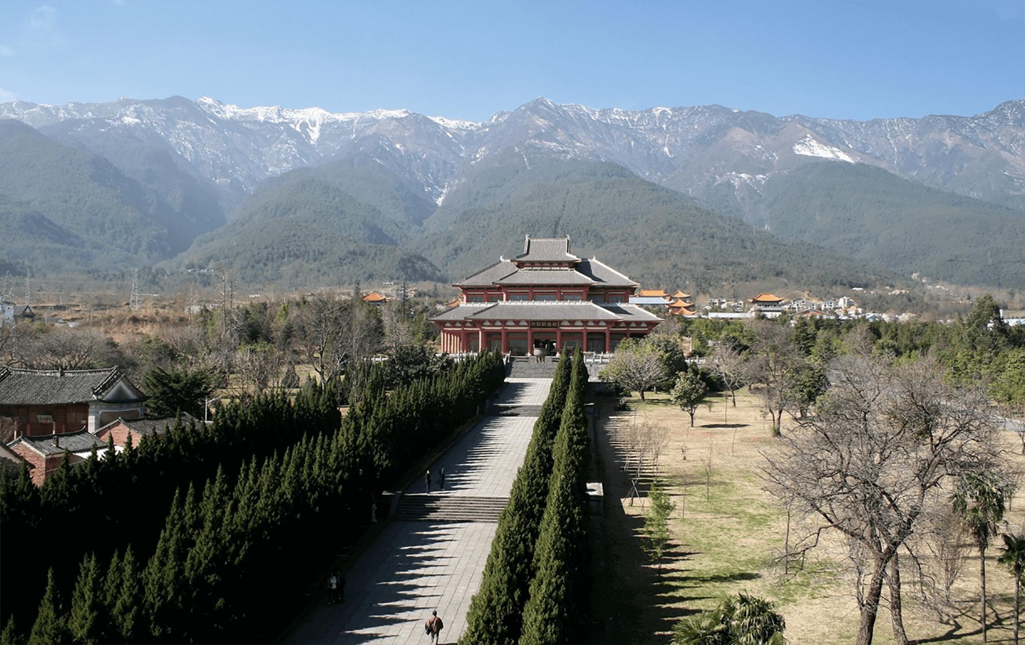 Reise in Yunnan in China. Eine lange Strasse führt zu einem chinesischen Tempel, im Hintergrund sind schneebedeckte Berge zu sehen.