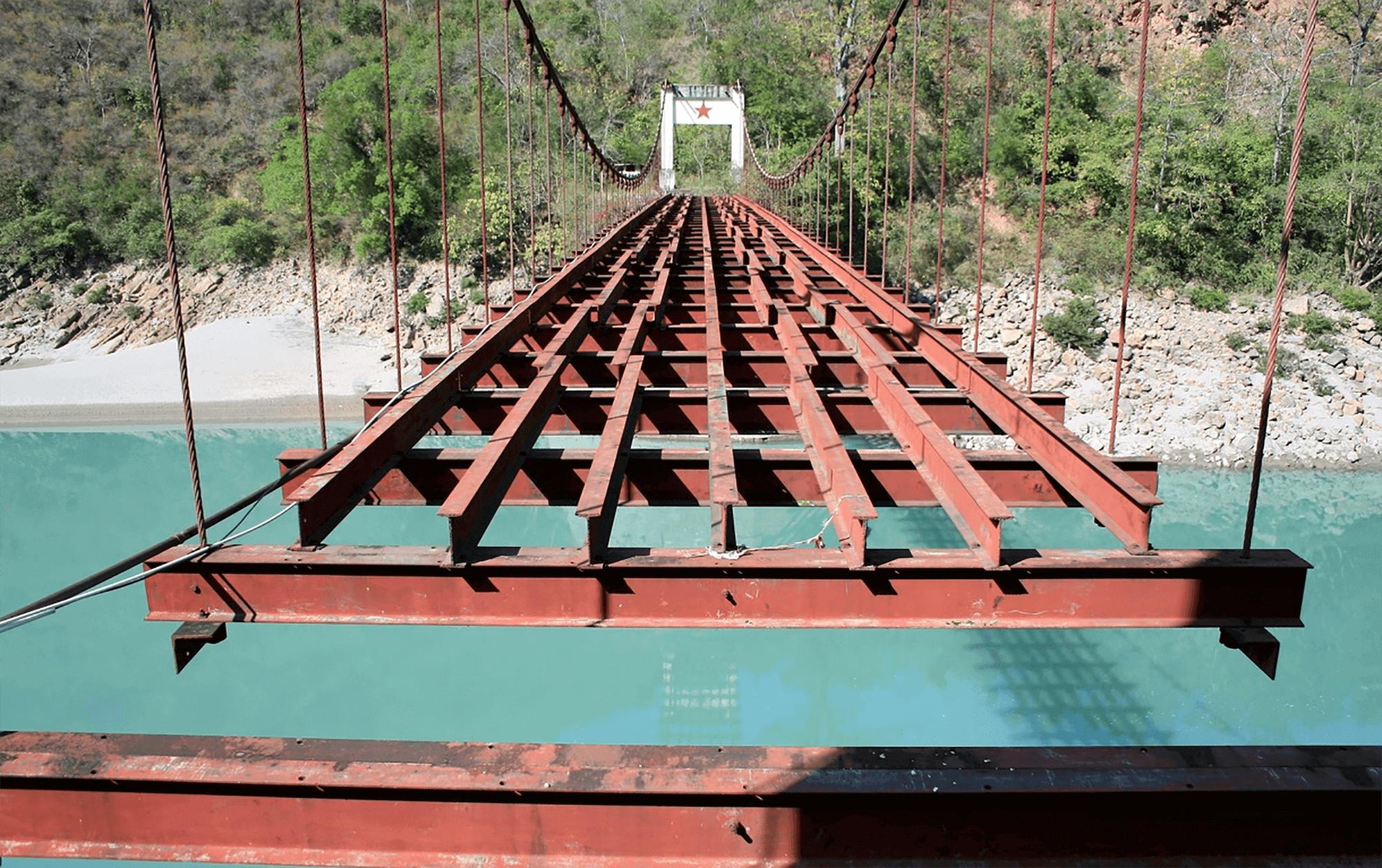 Reise in Yunnan in China. Eine rote Brücke führt über einen breiten Fluss an ein mit Büschen und Bäumen bewachsenes Ufer.