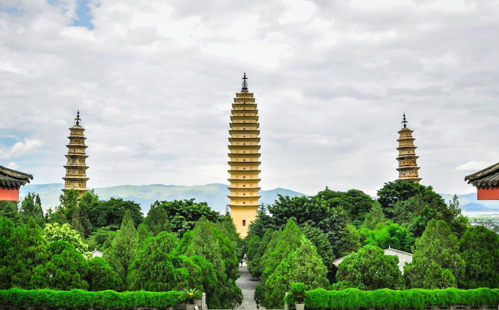 Reise in Yunnan in China. In der Stadt Dali ragen drei hohe Pagoden über eine üppigen Parkanlage.