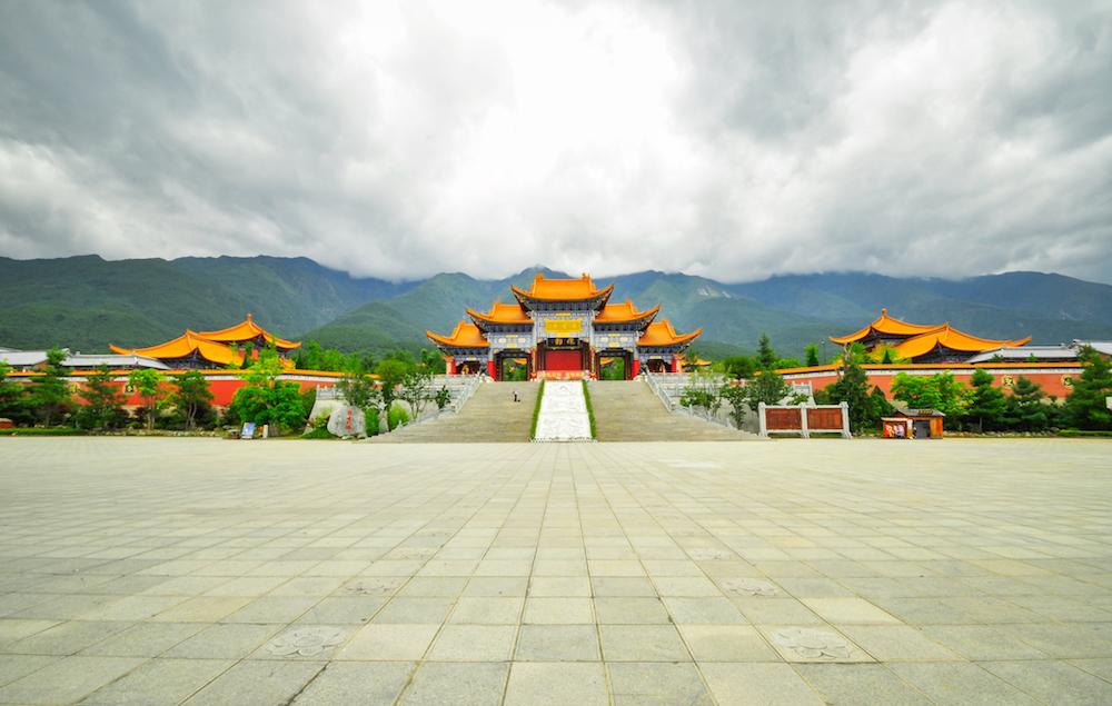 Reise in Yunnan in China. Ein weitläufiger Platz liegt leer vor einem chinesischen Tempel aus der Song Dynastie in der Stadt Dali.