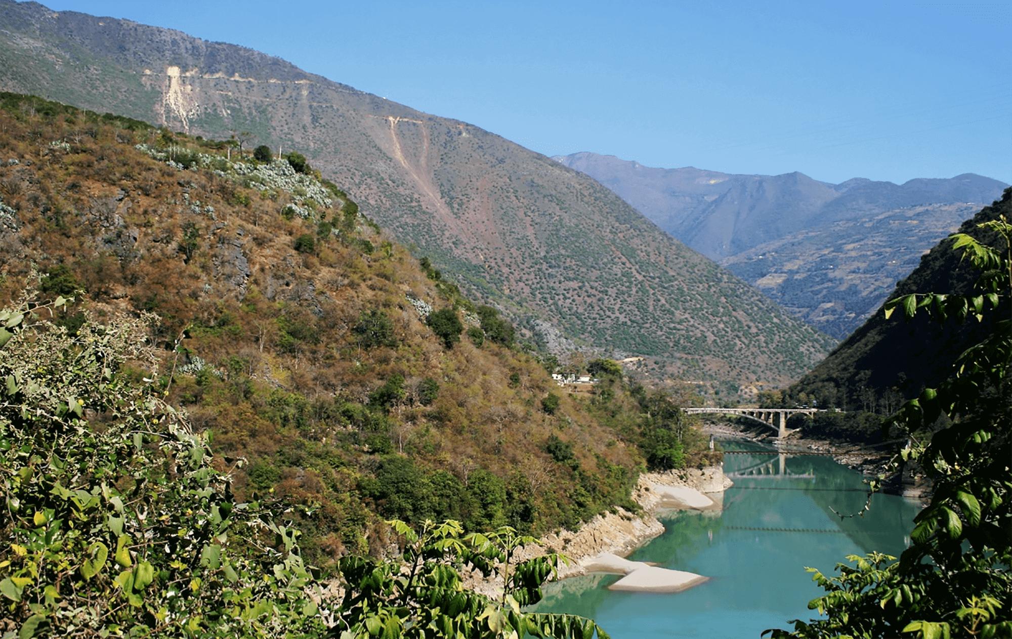 Reise in Yunnan in China. Ein Fluss fliesst durch ein Tal und wird in der Ferne von einer Brücke überspannt. Die Berghänge sind mit Bäumen und Sträuchern bedeckt.