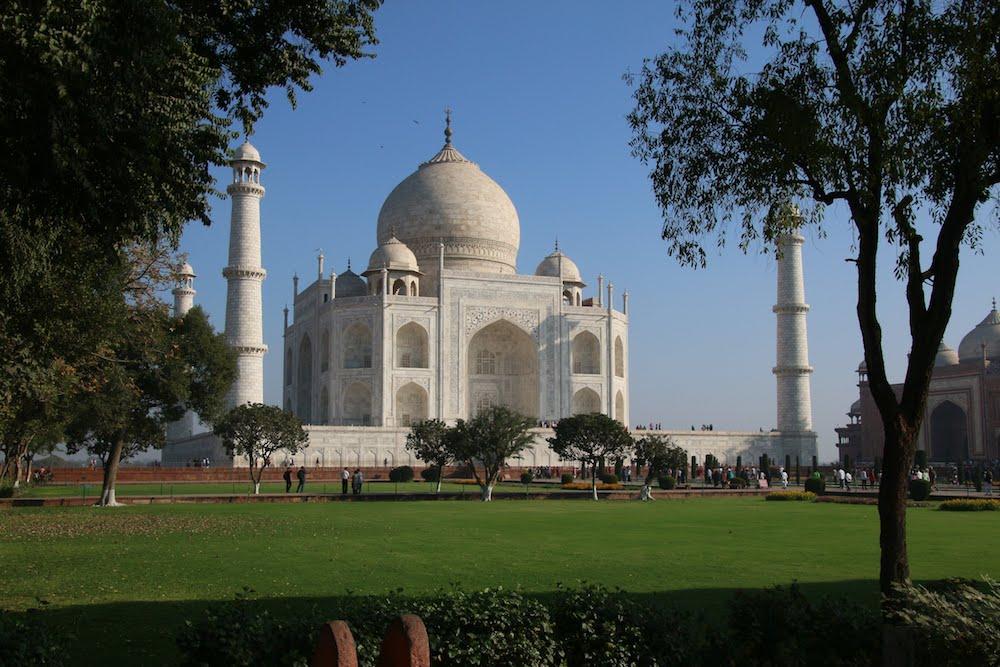 Reise in Indien in Asien. Das Taj Mahal Mausoleum in Agra wird von der Morgensonne beleuchtet, davor breitet sich der üppige Garten aus