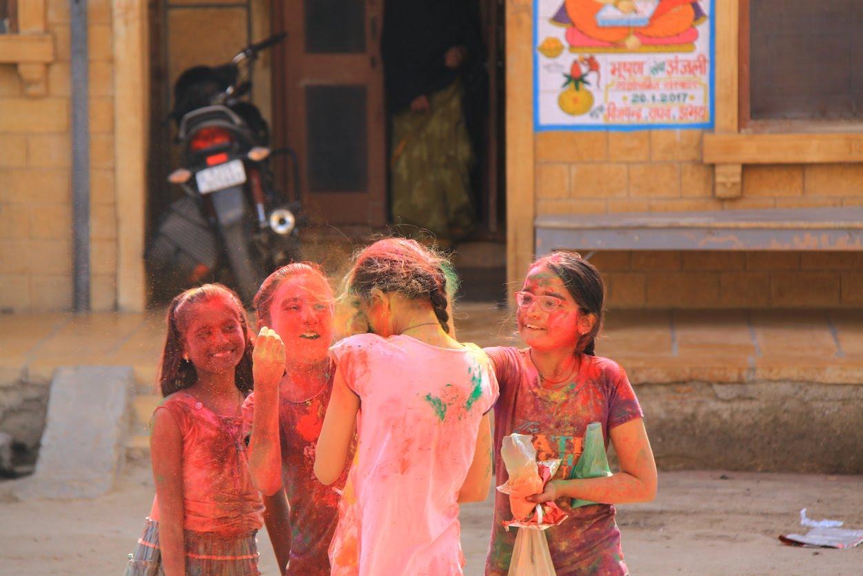 Reise in Indien in Asien. Vier junge Mädchen sind vom Holi Festival von Kopf bis Fuss mit Farbe bedeckt und bewerfen sich gegenseitig mit dem Pulver.