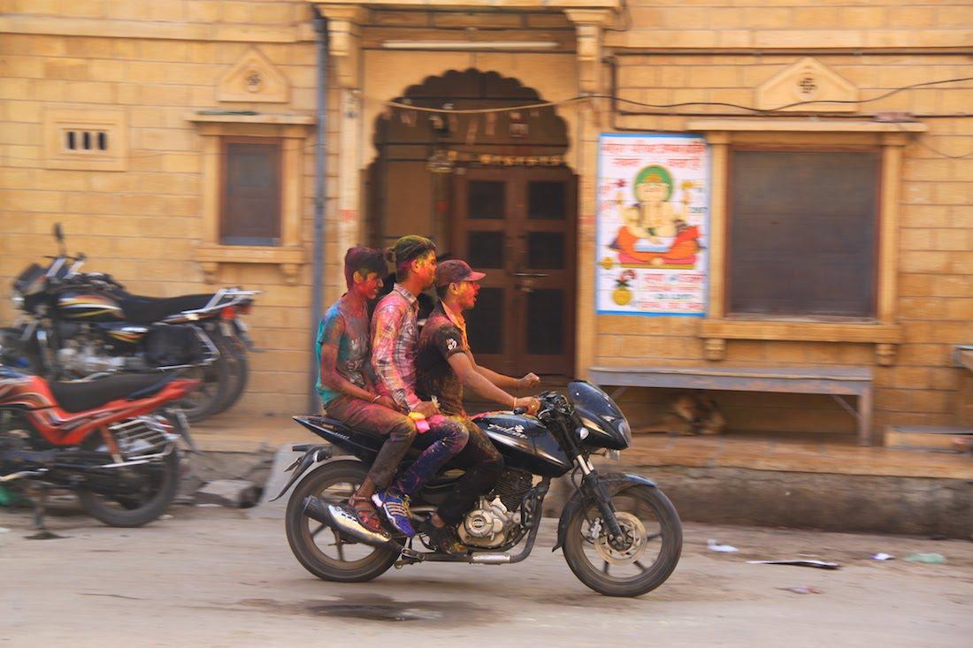 Reise in Indien in Asien. Drei von Kopf bis Fuss mit Farbe bedeckte junge Männer fahren auf einem Motorrad durch eine Strasse.