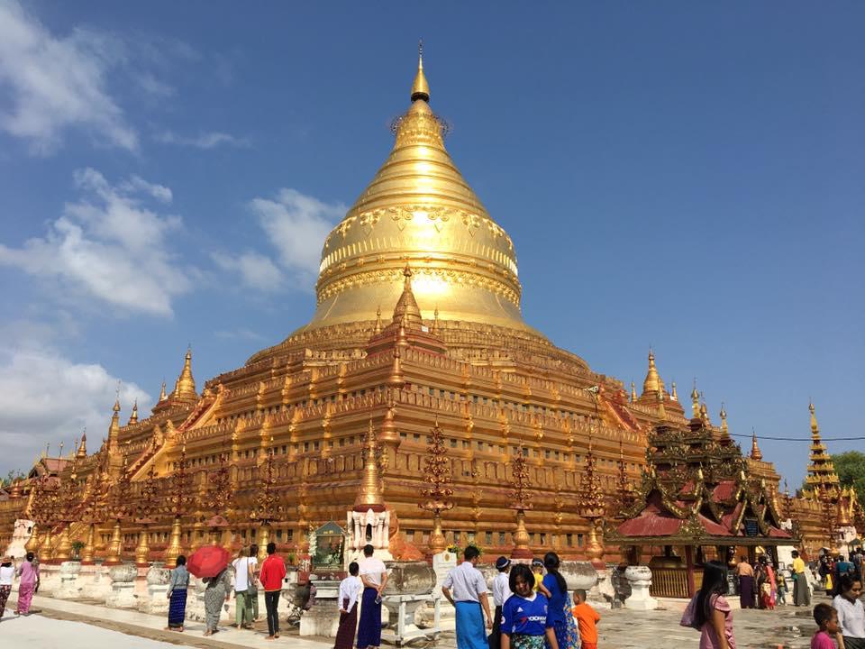 Reise in Myanmar in Asien. Die goldene Shwezigon Pagode in der Tempelstadt Bagan ragt vor einigen Besuchern empor.
