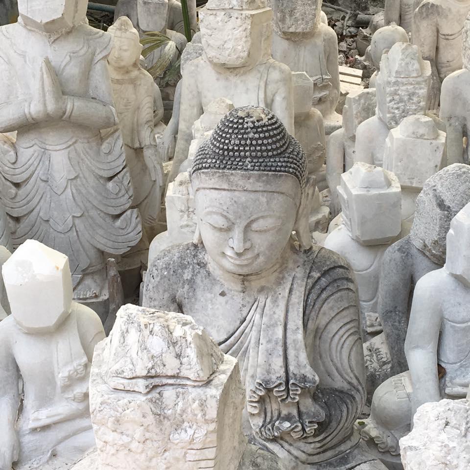 Reise in Myanmar in Asien. Weisse Buddha Statuen aus Stein reihen sich aneinander - bei einigen wurden die Köpfe noch nicht bearbeitet.