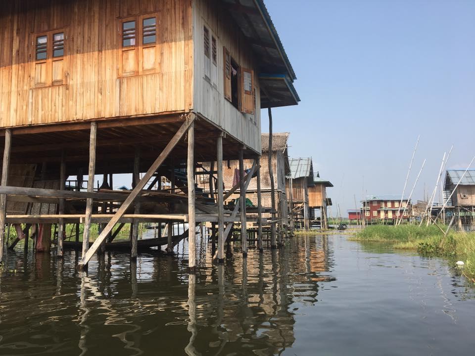 Reise in Myanmar in Asien. Blick vom Wasser aus auf ein Dorf auf Stelzen, mitten auf dem Inle See. Zwischen den Häusern schwimmen Wasserpflanzen.