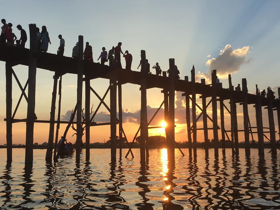 Reise in Myanmar in Asien. Menschen überqueren die U-Bein Brücke, während die Sonne untergeht.