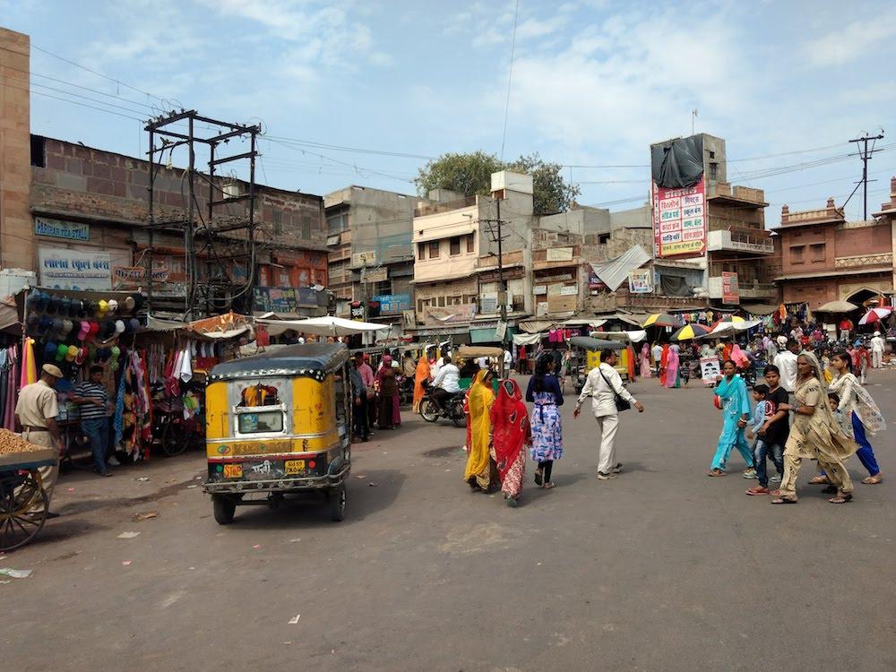 Reise in Indien in Asien. Auf einer Strassenkreuzung in Indien tummeln sich Tuk Tuks, einheimische Familien, Motorräder und Marktstände