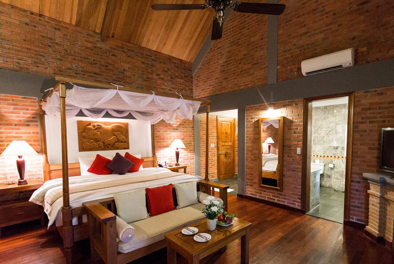 Reise in Vietnam in Asien. Im stilvoll eingerichteten Honeymoon Bungalow des Pilgrimage Village Resort in Hue steht ein grosses Bett mit weissen Vorhängen und ein Sofa auf dem Holzboden.