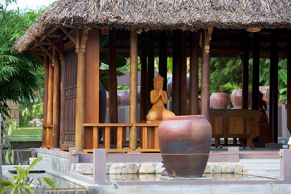Reise in Vietnam in Asien. Blick auf den Spa und Wellnessbereich des Prilgrimage Village Resorts in Hue, ein offenes Haus mit Bambusdach und hölzernen Buddhastatuen.