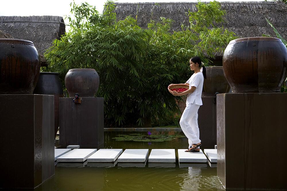 Reise in Vietnam in Asien. Im Spa des Pilgrimage Village Resorts in Hue läuft eine einheimische Frau mit einem Korb voller Blüten über Steine im Wasser.