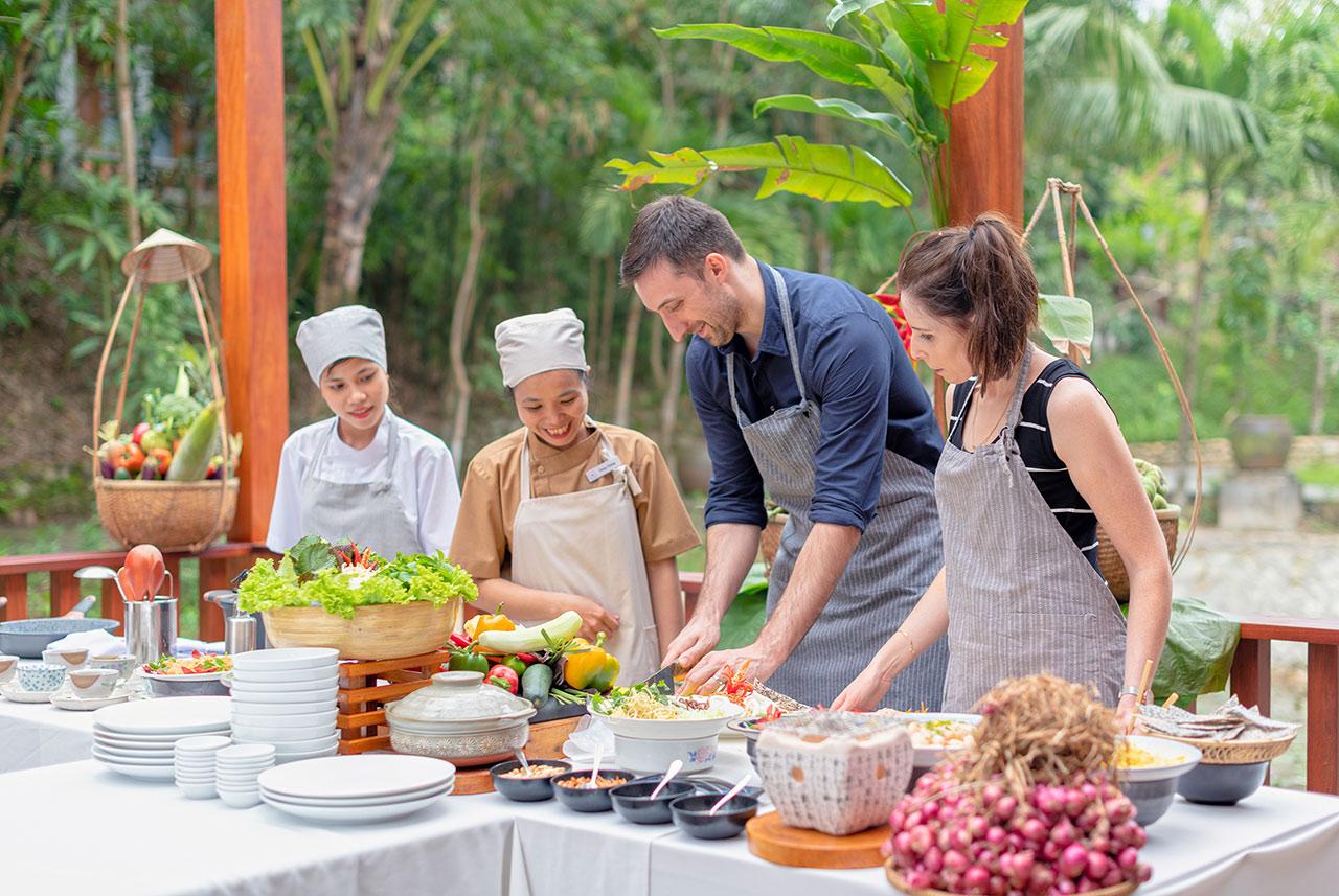 Reise in Vietnam in Asien. Zwei Touristen kochen zusammen mit zwei einheimischen Frauen ein asiatisches Gericht. Der Tisch ist reich gedeckt mit frischem Gemüse und Gewürzen.