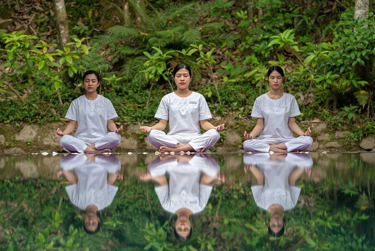 Reise in Vietnam in Asien. Drei einheimische Frauen in weisser Leinenkleidung sitzen im Schneidersitz vor einem Pool und meditieren.