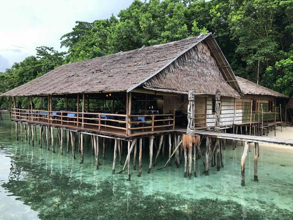Reise in Raja Ampat in Indonesien. Das Restaurant des Papua Paradise Eco Resort ist ein charmanter Bungalow, der auf Stelzen im seichten, türkisen Wasser steht.