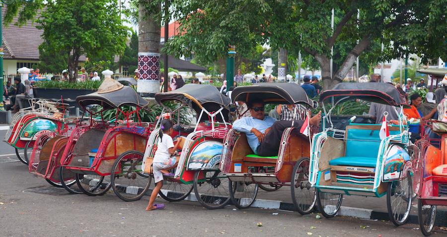 Reise in Java und Sulawesi in Indonesien. In einer Stadt stehen einige Fahrrad Rikschas und ein Fahrer wartet auf Kunden.