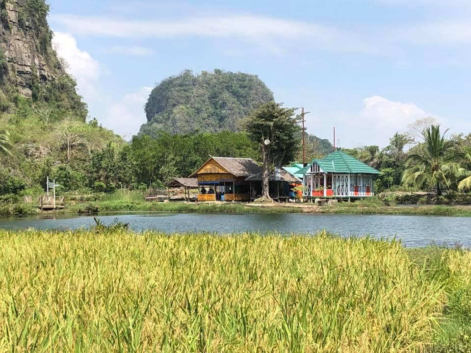 Reise in Sulawesi in Indonesien. Blick auf zwei Bungalows der Eco Lodge Rammang Rammang, umgeben von Wasser und üppiger Natur und Bergen.