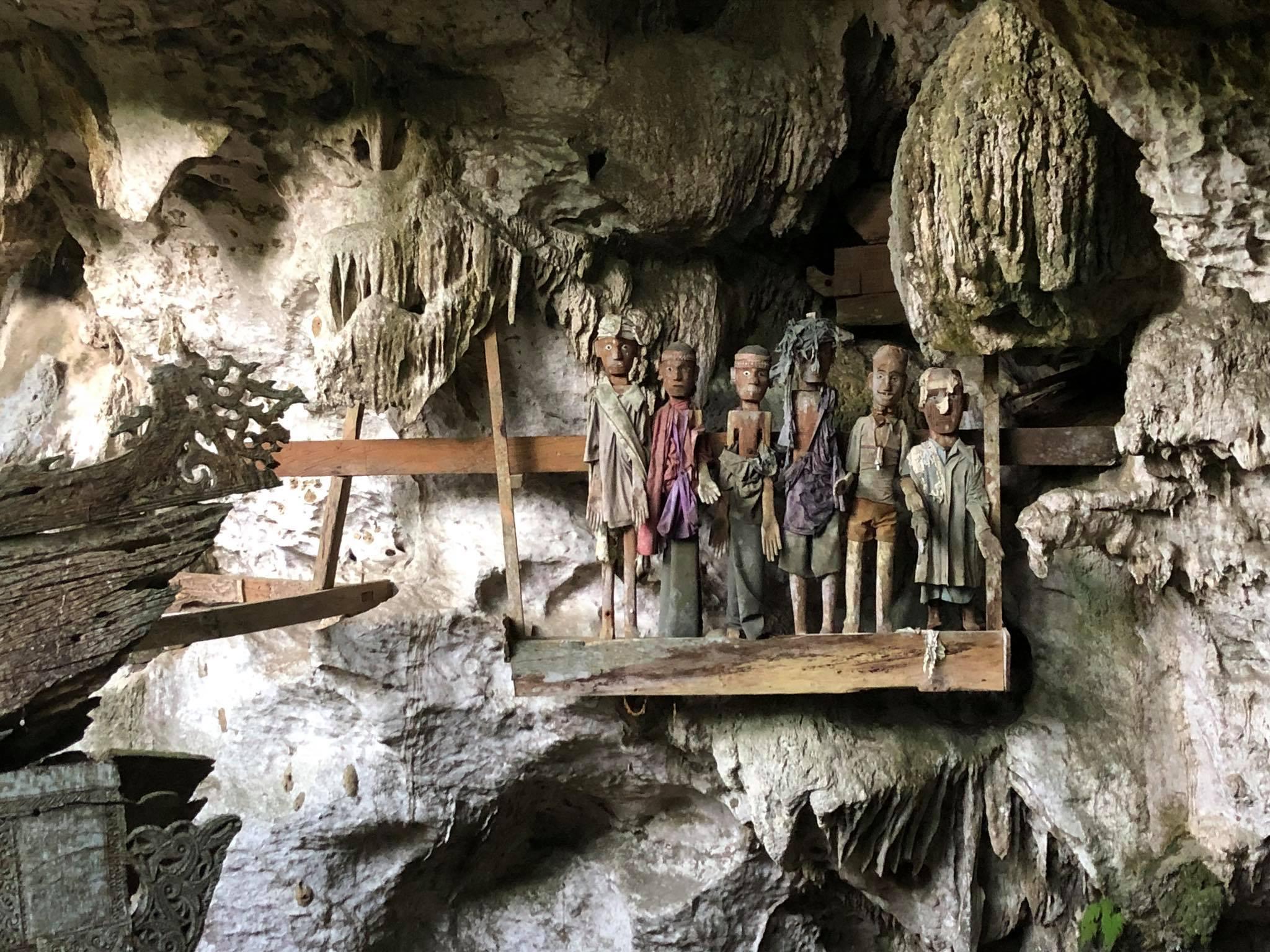 Reise in Sulawesi in Indonesien. In einer Höhle in der Provinz Tana Toraja stehen einige mit Stoff bekleidetet Holzpuppen.