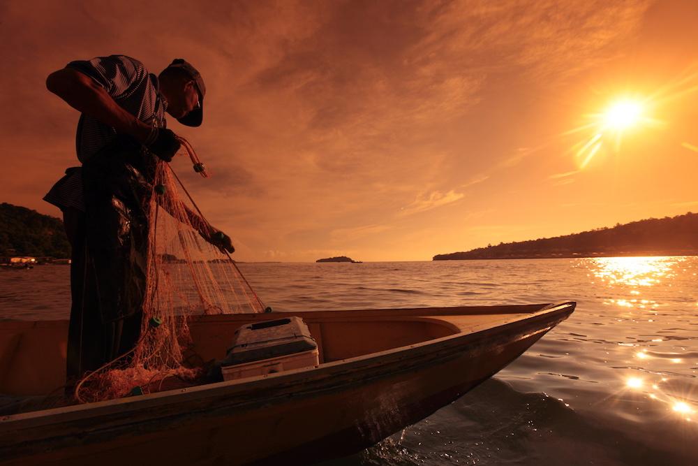 Reise in Sulawesi in Indonesien. Stimmungsbild mit einem Fischer, der von seinem Boot aus in den frühen Morgenstunden sein Netz auswirft.