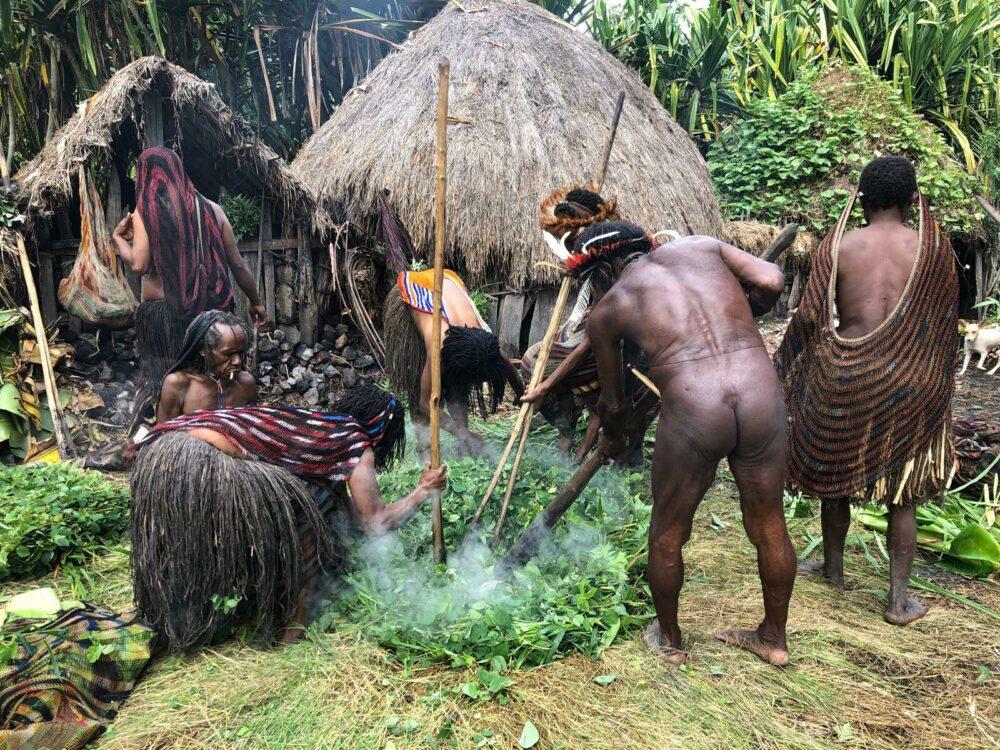 Reise in West Papua in Indonesien. Im Baliem Tal stampfen Stammesmitglieder im Rahmen des Schweinefests brennende Kräuter und Pflanzen mit langen Stäben.