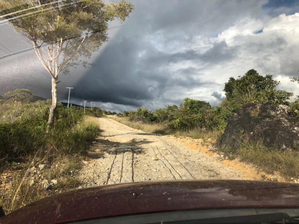 Reise in West Papua in Indonesien. Eine Schotterstrasse führt durch eine abgelegene Landschaft, Strommasten reihen sich entlang der Strasse auf, am Himmel stehen Gewitterwolken.