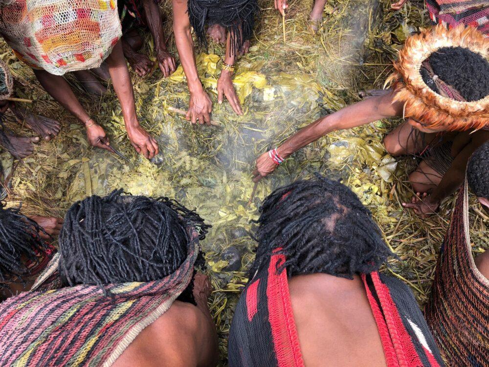 Reise in West Papua in Indonesien. Viele Stammesmitglieder, manche mit Kopfschmuck, stehen um eine Feuerstelle gebückt und kochen gemeinsam.