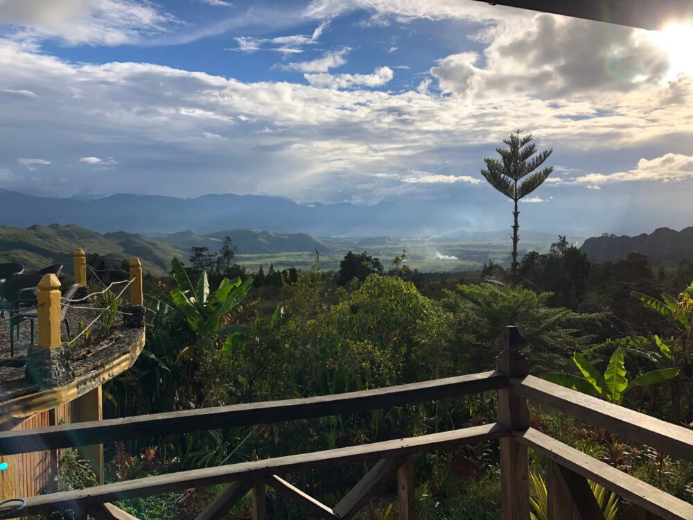 Reise in West Papua in Indonesien. Von der Terasse des Baliem Valley Resort geniesst man einen weiten Ausblick über die grüne, üppige Hügellandschaft.