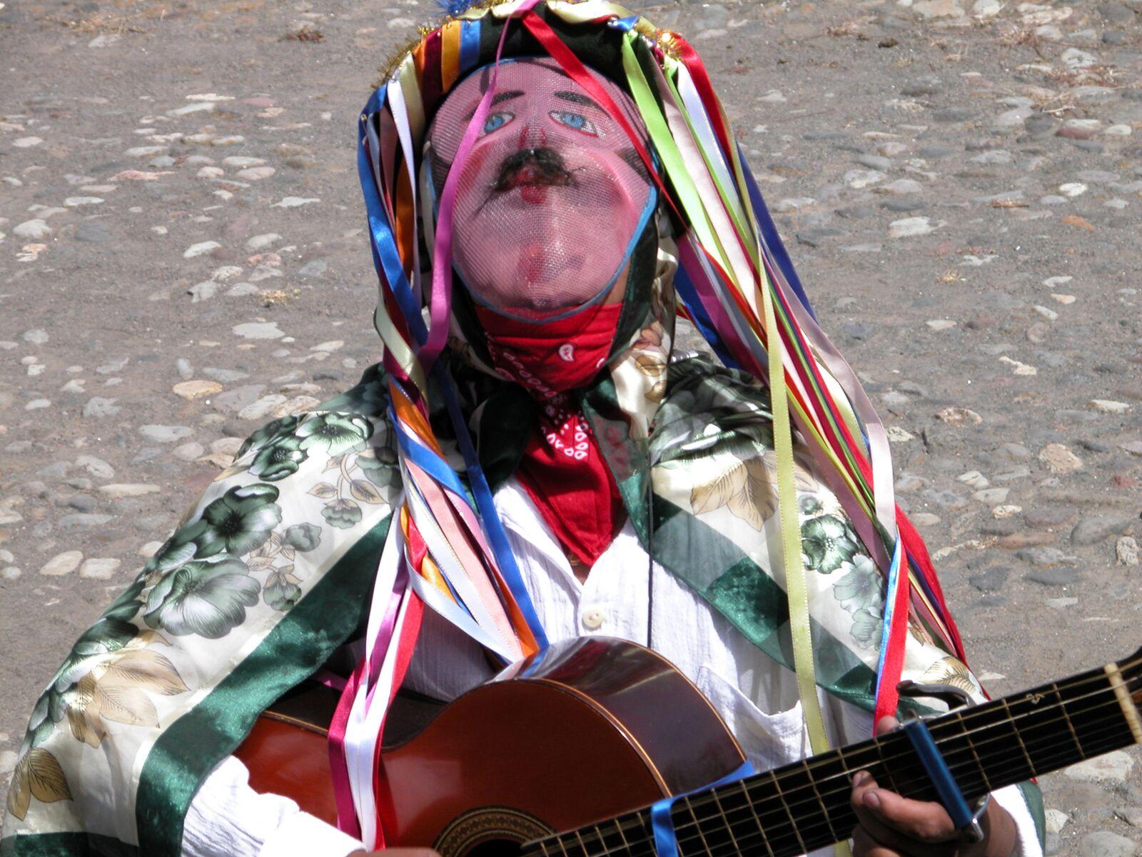 Reise in Galapagos und Ecuador in Südamerika. Ein einehimischer Mann in traditioneller Kleidung spielt Gitarre auf der Strasse.
