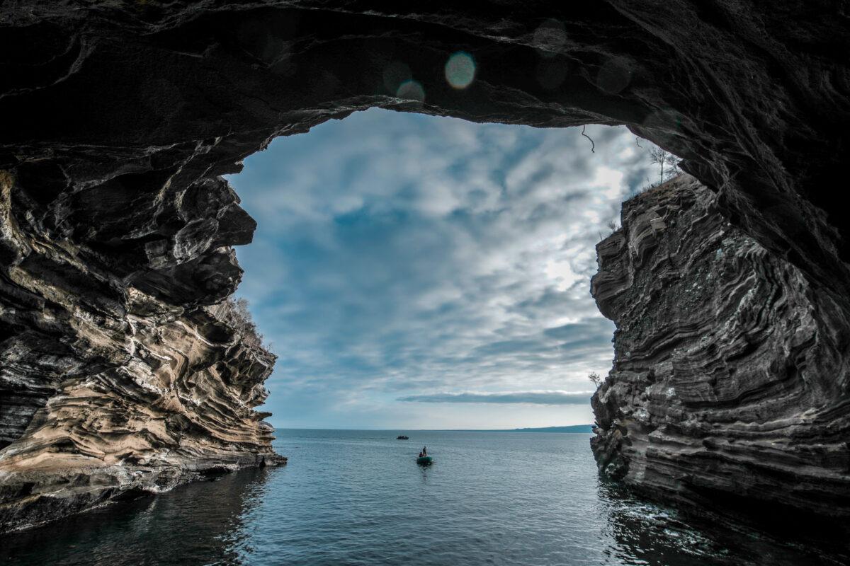 Reise in Galapagos und Ecuador in Südamerika. In einer Bucht hat sich eine Höhle zu einem natürlichen Tunnel gebildet, das Meer schimmert dunkel, der Himmel ist bewölkt.