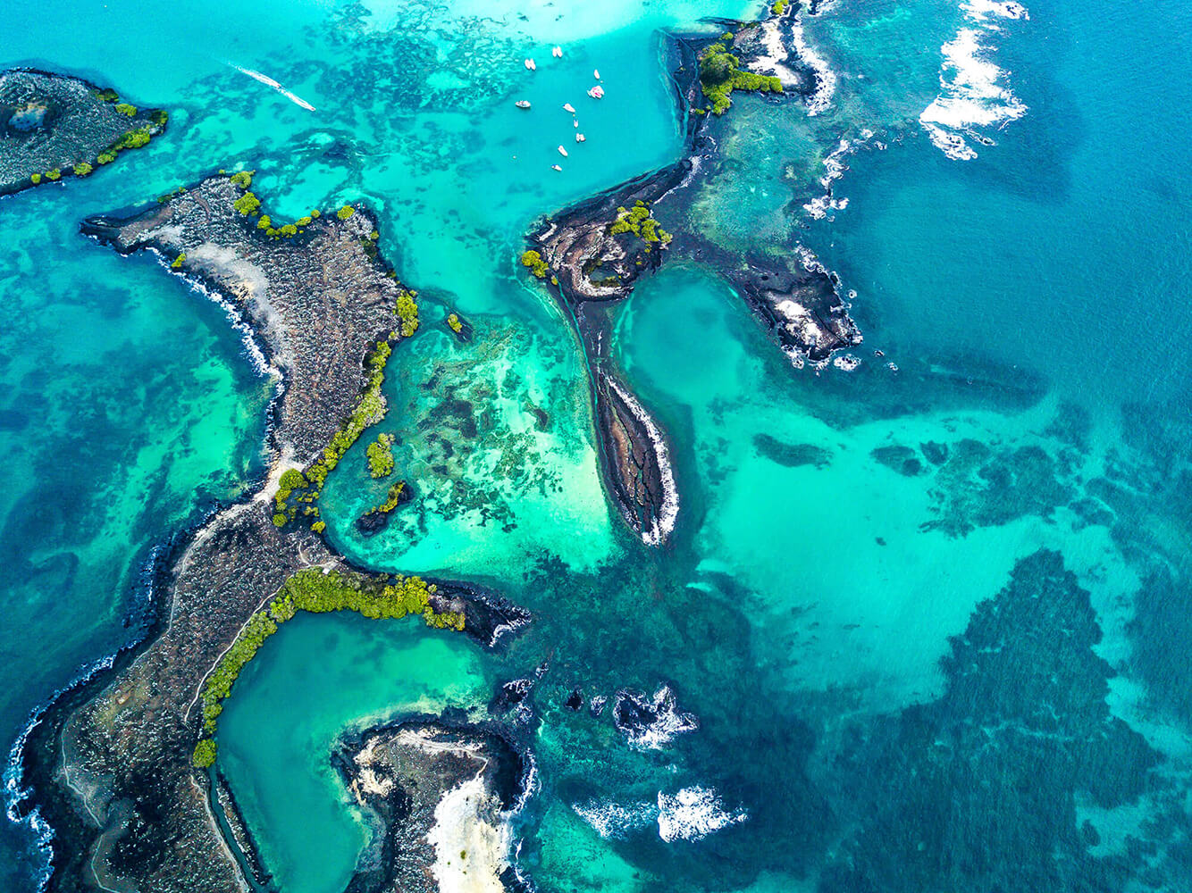 Reise in Galapagos und Ecuador in Südamerika. Aus der Luft sind einige kleine Vulkaninseln, Riffe und vereinzelte Boote zu erkennen.