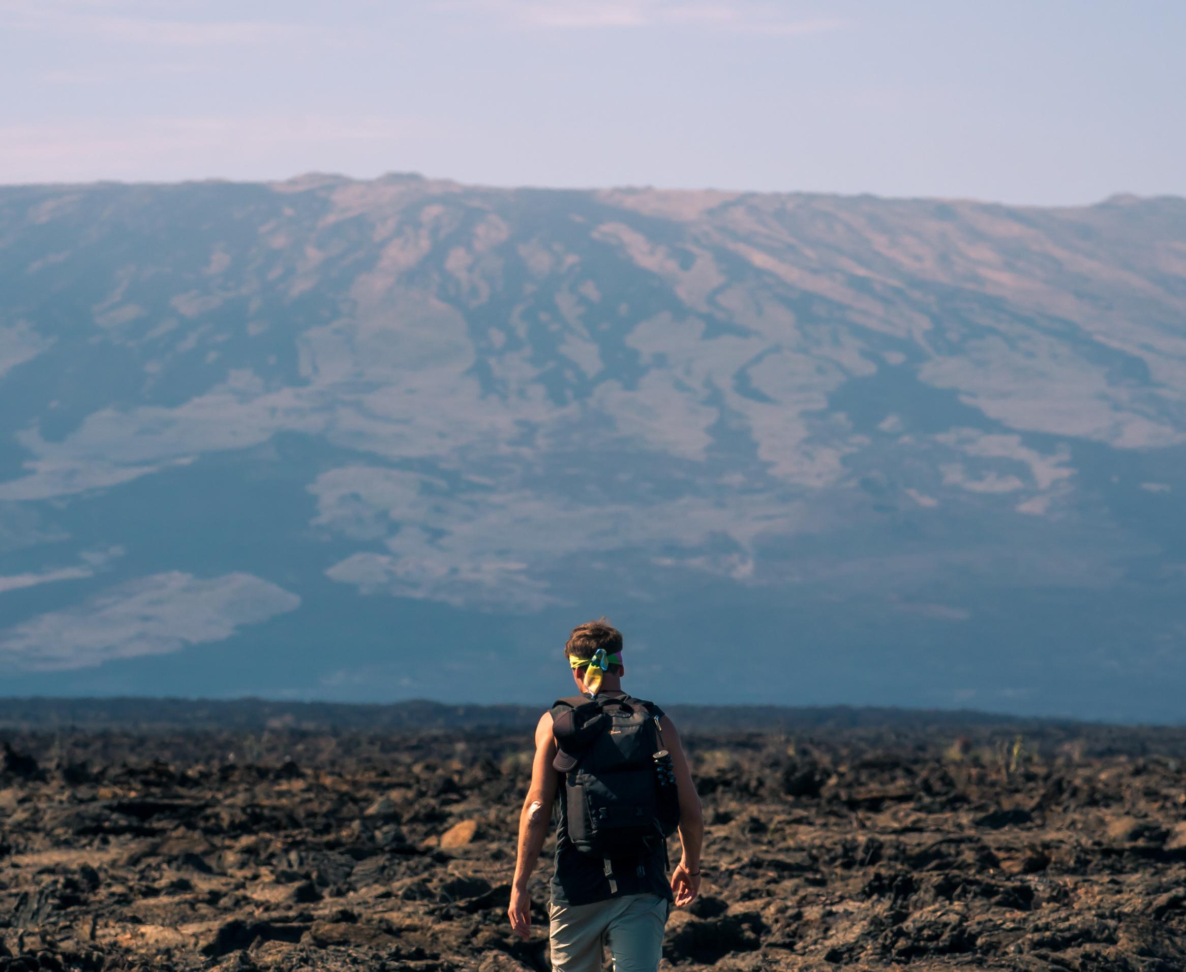 Reise in Galapagos und Ecuador in Südamerika. Ein Mann unternimmt eine Vulkanwanderung und läuft in Richtung der Berge im Hintergrund.