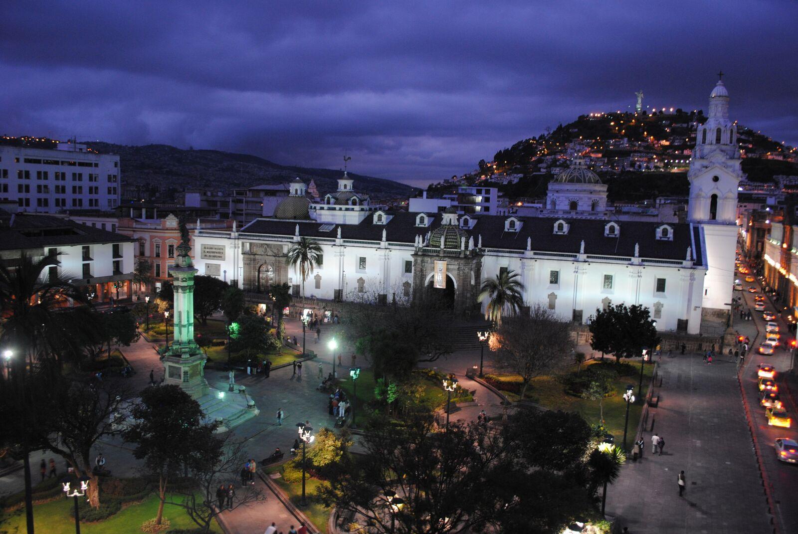 Reise in Galapagos und Ecuador in Südamerika. Die Stadt Quito bei Nacht, eine Kirche wird beleuchtet, in den Strassen fahren Autos.