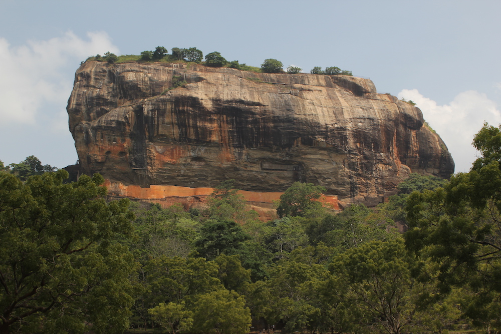 Reise in Sri Lanka in Asien. Der Monolith Sigirya, ein UNESCO Weltkulturerbe und auch Löwenfelst genannt, ragt majestätisch aus dem Urwald empor.