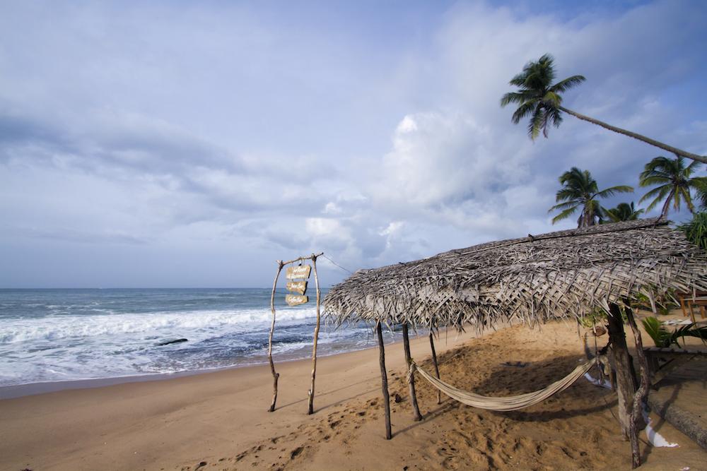 Reise in Sri Lanka in Asien. Am Strand von Tangalle steht ein kleiner Verschlag mit einem Dach aus Bambus und einer Hängematte darunter, die Wellen brechen sich am Strand.