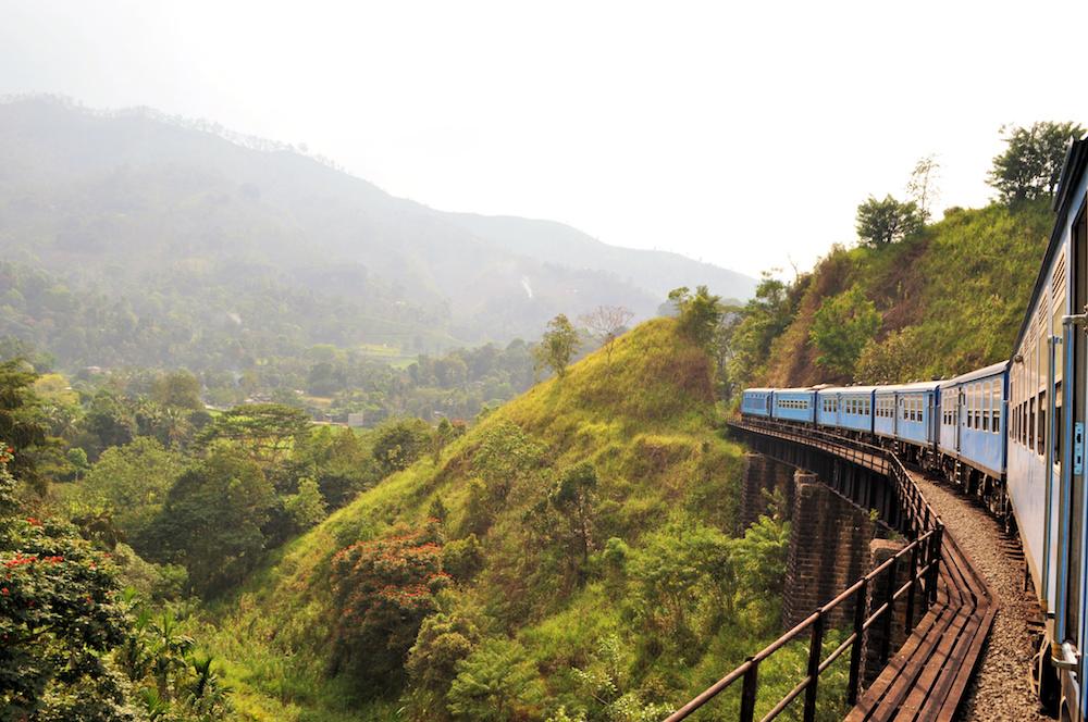 Reise in Sri Lanka in Asien. Ein Zug fährt den üppig bewachsenen Hügeln entlang in Richtung der Stadt Ella.