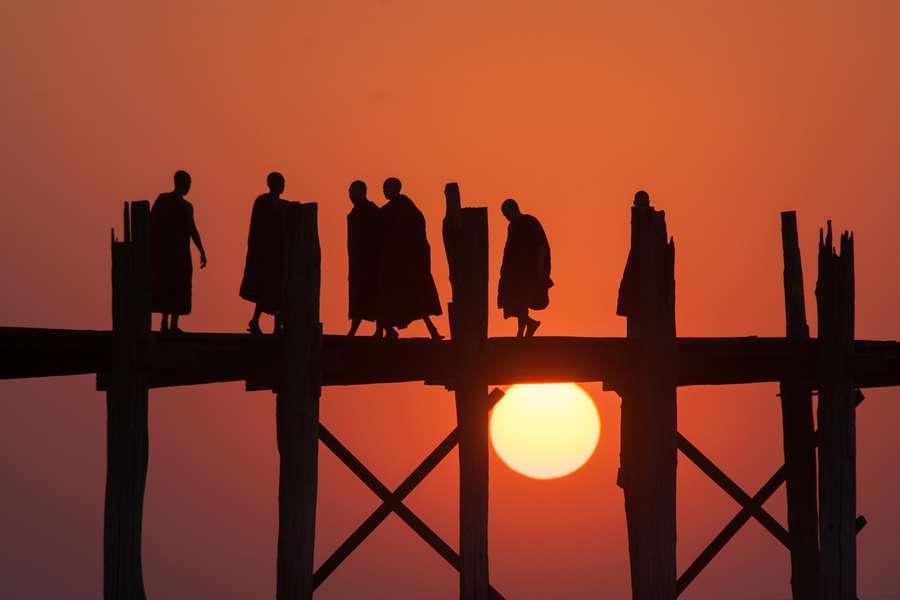 Reise in Myanmar in Asien. Stimmungsbild mit der U Bein Brücke, die sich klar vor der unterghenden Sonne abzeichnet. Einige buddhistische Mönche überqueren diesen Abschnitt der Brücke.