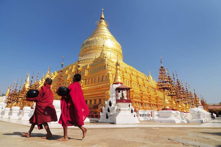 Reise in Myanmar in Asien. Zwei junge, buddhistische Mönche in roten Gewändern laufen am Fuss der goldenen Shwezigon Pagode in Bagan entlang.