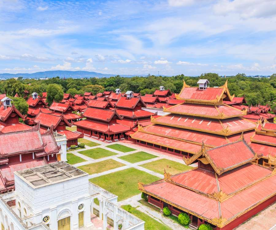 Reise in Myanmar in Asien. Die roten, mit goldenen Verziehrungen gesäumten Dächer des weitläufigen Königspalast in Mandalay leuchten hell in der Mittagssonne.