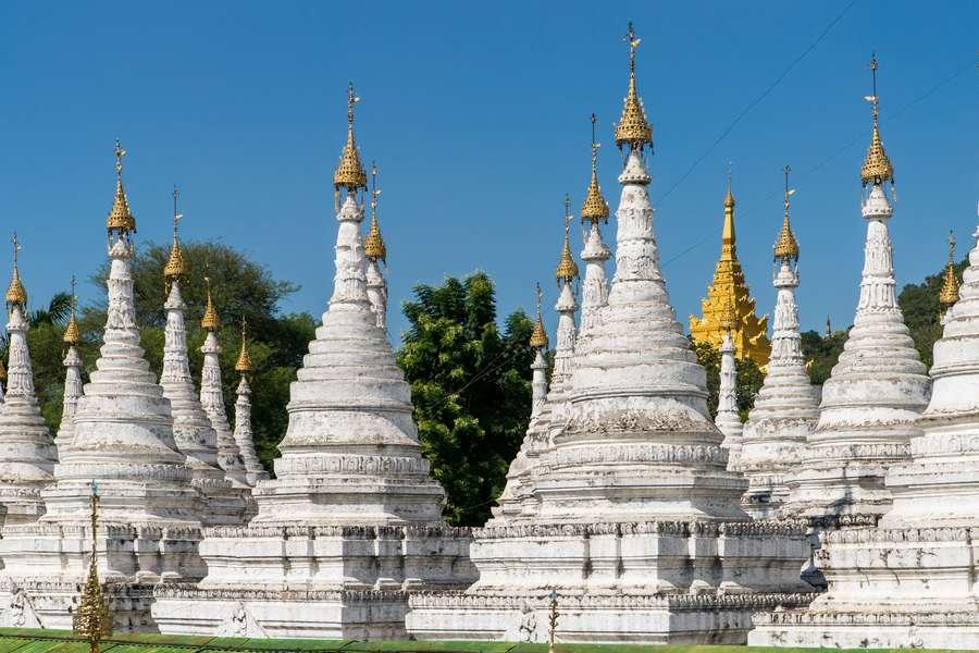 Reise in Myanmar in Asien. Zahlreiche weisse Stupas der Sanamuni Pagode in Mandalay stehen aneinandergereiht mit ihren goldenen Verziehrungen.
