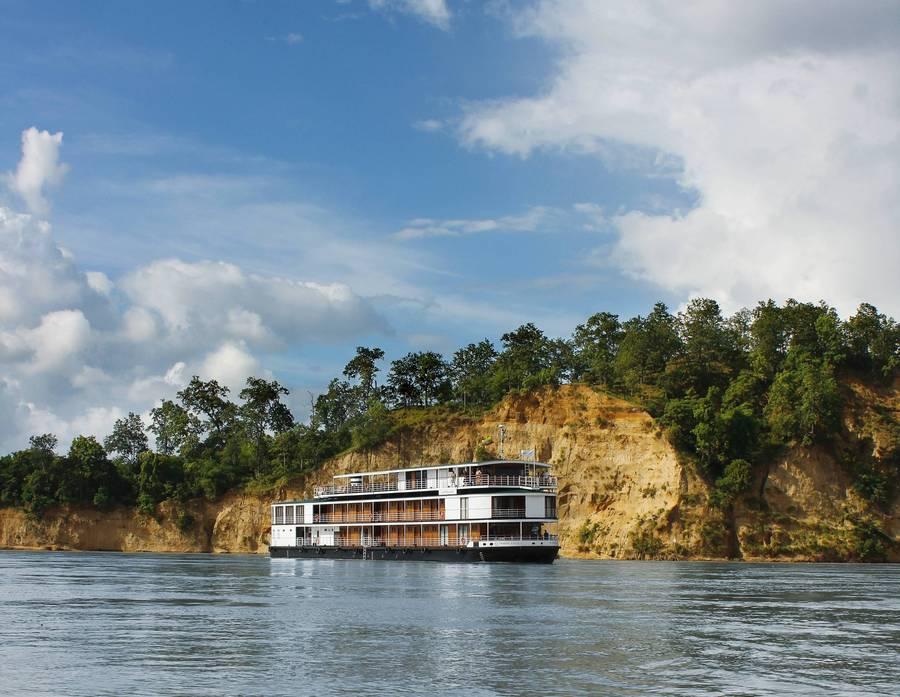 Reise in Myanmar in Asien. Das Schiff Thurgau Exotic 3 von Thurgau Travel fährt dem Fluss Irrawaddy in Myanmar entlang, im Hintergrund erhebt sich eine Felswand.