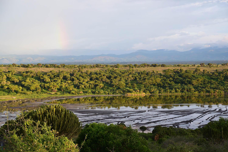 Reise in Uganda in Afrika. Ausblick auf den Queen Elizabeth Nationalpark mit einem grossen Wasserloch und vielen Bäumen, im Hintergrund schimmert ein Regenbogen.