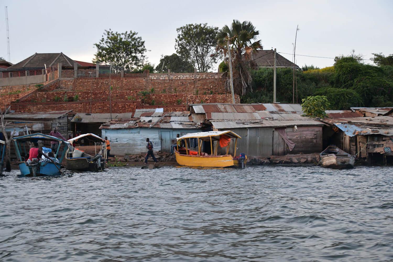 Reise in Uganda in Afrika. Ein Dorf an der Küste des Victoria See mit Wellblechhäusern und Fischerbooten.